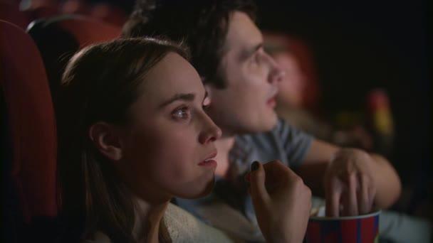 Fiatal pár élvezi a film a moziban. Pár eszik a pattogatott kukorica és film