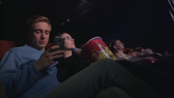 Young man using smartphone in movie theatre. Young man using phone in cinema