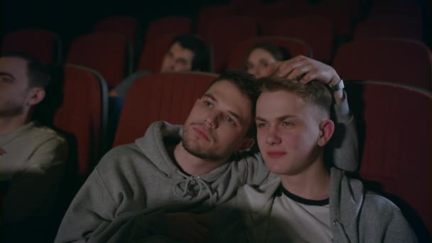 Couple gays embracing in movie theater. Homosexual men embrace in movie theatre