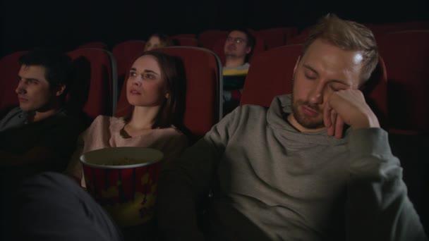 Man sleep at cinema movie. Guy sleeping at cinema date. People watch boring film