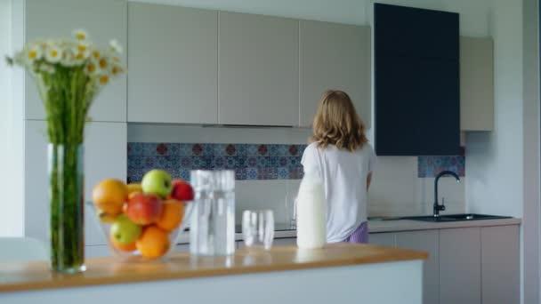 Mladá žena připravuje ovesné kaše v kuchyni. Dívka dává láhev mléka