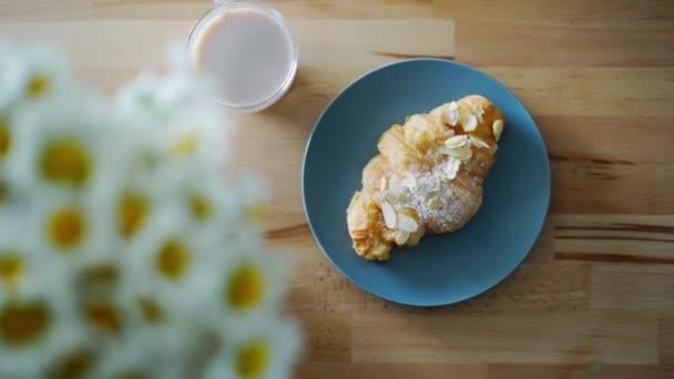 Francouzský croissant s plátky mandlí. Detailní záběr žena ruku s croissantem