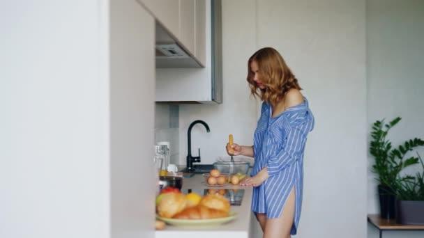 Smyslná žena, šlehání vajec ve skleněné mísy na vaření omeletu. Snídaně vejce