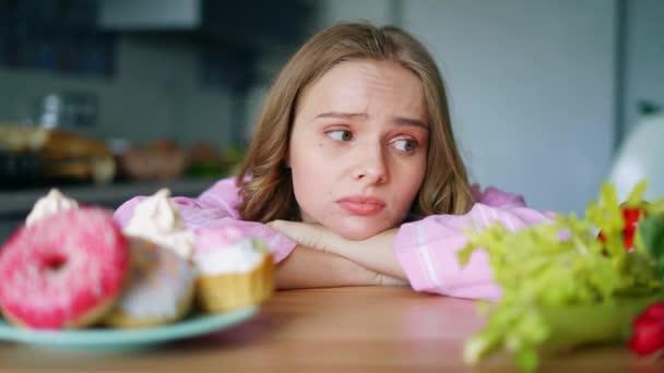 Mladá žena, volba mezi zeleninu a sladkosti. Smutná dívka hledá