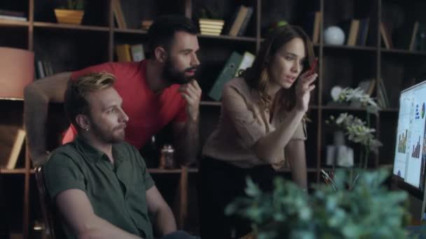 Obchodní analytik tým hledá diagramy na počítači v kanceláři. Úspěšný tým