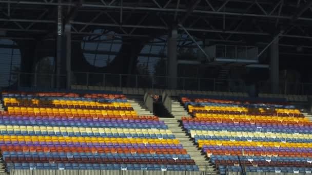 Fotbalový stadion s někým z tribuny. Prázdné různé barvy křesel
