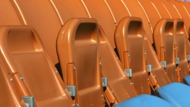 Řádky v stadion s skládací židle sezení. Detailní záběr sednu oranžové a modré