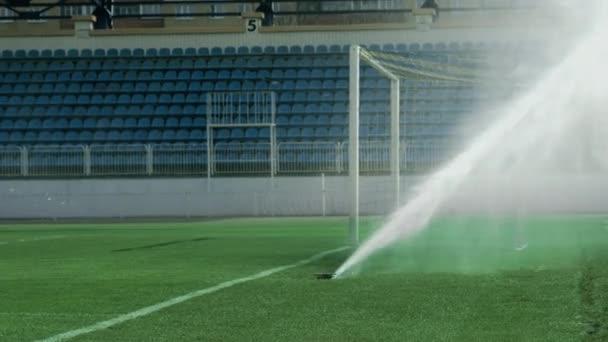 Vodní trysky kropení na zelené trávě fotbalového stadionu. Sportovní oblasti zalévání