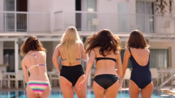 Summer girls jumping pool. Hot summer pool party. Back view of jumping girls in swimming pool water. Enjoy summer lifestyle. Summer vacation. Enjoy fun at resort. Female rest