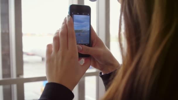 Smartphone video a repülőgép felszállás. Nő használata mobil videó repülőtéren