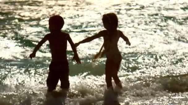 I bambini si divertono al tramonto onde. Felice vacanza. I bambini godere dellacqua