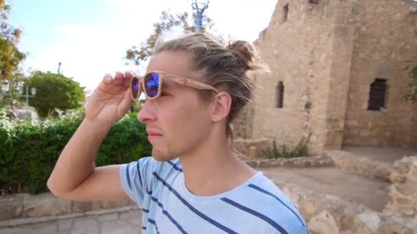 Bokovky muž nosí sluneční brýle. Cestovatel v tropických city