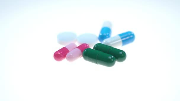 Farmaceutické pilulky otočení na bílém pozadí. Lékařské tablety