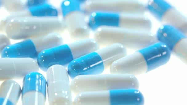 Medikamentenpillen. Nahaufnahme von weißen und blauen Kapseln, die sich auf weißem Tisch drehen