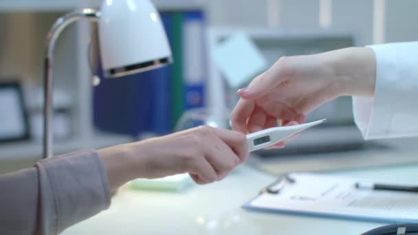 Patient give doctor thermometer at workplace. Doctor control fever thermometer