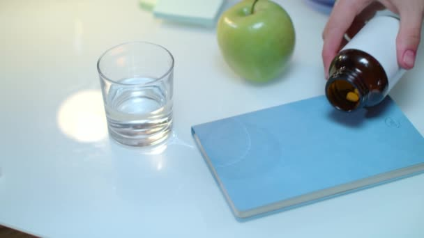 Hand pour tablet and capsules from bottle on table. Healthy medicine concept