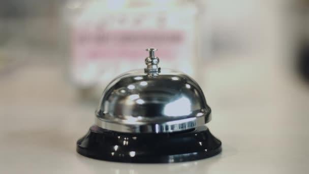 Menschliche Hand läuten Silber-Service an der Rezeption des Hotels