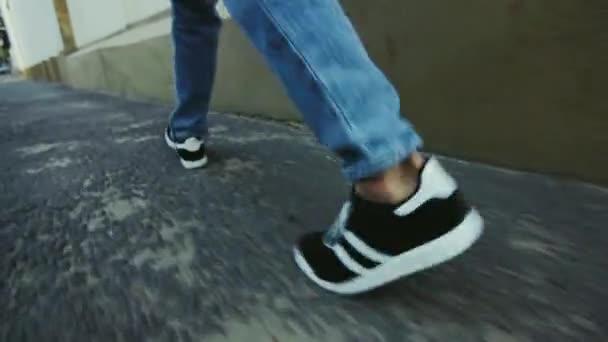 Guy v teniskách na asfaltový chodník města. Muž nohy chůzi v městě