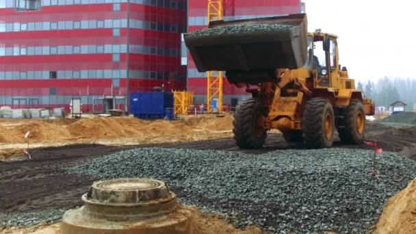 Bulldozer unloading broken stone on ground. Infrastructure construction