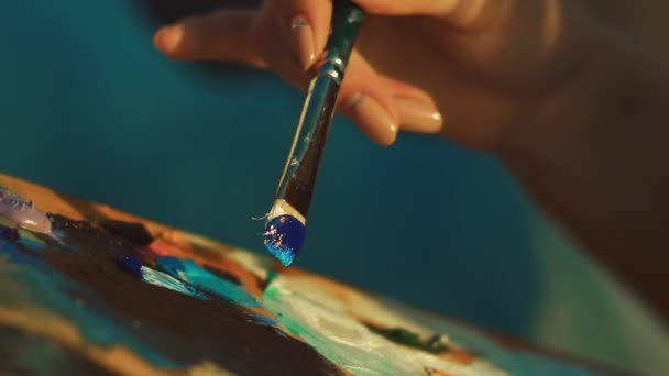 Female artist mixing paints on palette with brush. Woman hand holding paintbrush