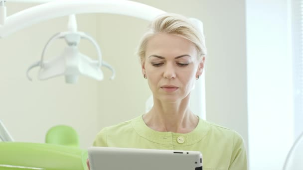 Woman dentist using tablet computer. Dental professional using tablet pc