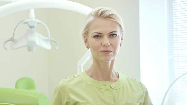 Stomatologo sorridente che Mostra dentifricio e spazzolino da denti. Medico della donna che mostra i denti prodotti per la cura. Ritratto di dentista della donna con accessori moderni per denti spazzolatura in studio dentistico