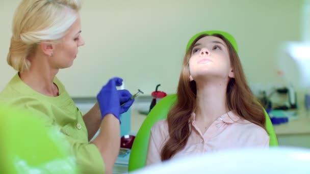 Zahnarzt, der die Zähne von Patienten mit zahnärztlichen Instrumenten untersucht. Arzt und Patient