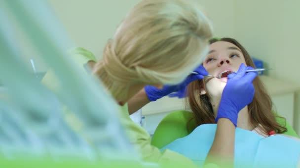 Young woman having regular teeth examination at family dentist