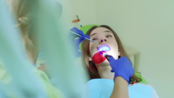 Tooth filling in dental clinic. Dentist working in patient oral cavity
