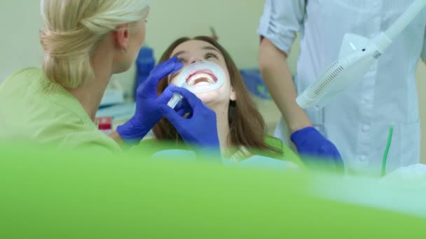Professional whitening teeth procedure in dental office. Dentist with assistant