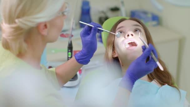 Processo di trattamento di denti in ufficio del dentista. Bionda dentista lavora con il paziente