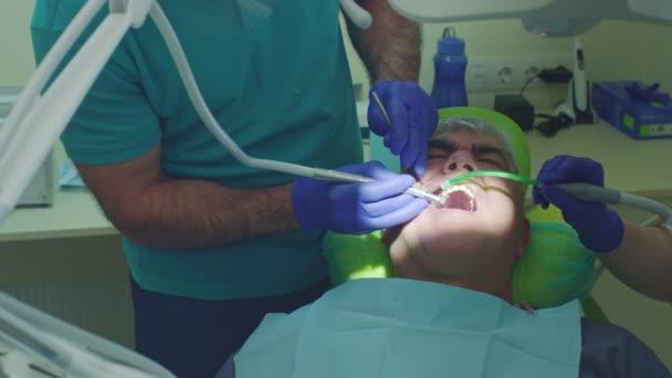 Léčba zubního kazu zuby. Zblízka senior zubař s asistentem vrtání zubů