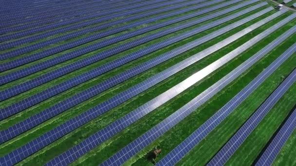 Hosszú sorok a fotovoltaikus napelemek a zöld mező, napsütéses napon. Légi táj a megújuló energia napelem modulok. Naperőmű összetett. Alternatív energiatermelés