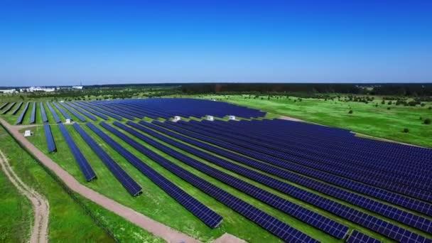 Fotovoltaické solární panely na zelené louce v slunečný den. Letecká krajina