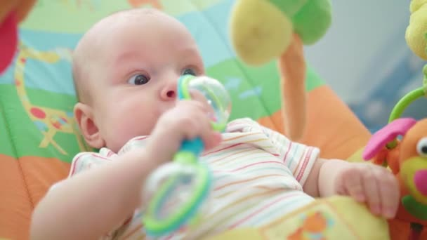 Portrét novorozené dítě hraje s hračkou. Zblízka chlapeček hraje hračka