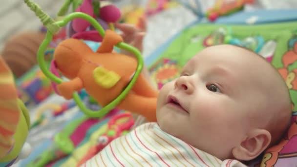 Roztomilé dítě bavit s hračkami. Zblízka šťastné děti leží na rozvoj mat