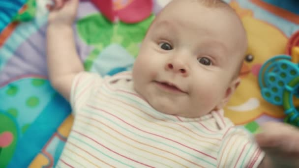 Portrét dítěte při pohledu na fotoaparát na barevné mat. Detailní záběr roztomilé dítě tváře