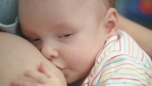 Stillen Babygesicht. lieblicher Säugling, der Muttermilch isst. Süße Mutterschaft