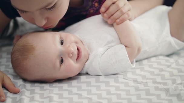 Sestra láska koncept. Detail dívky polibek usmívající se dítě. Kojenecká baby, usmívající se sestry polibek. Koncept krásné dětství. Portrét starší sestra políbit děťátko