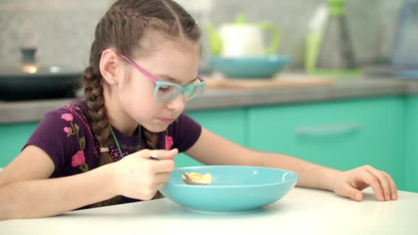 Girl eating cornflakes at kitchen. Portrait of child eating healthy food