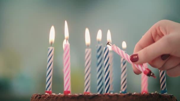 Nő kéz a gyertya lángja betesz a születésnapi torta. Égő gyertya, születésnapi torta