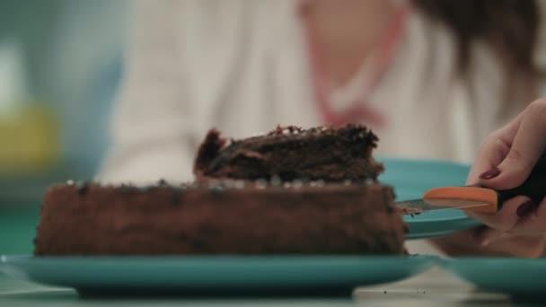 Zblízka ženské ruky dal sladký dort na desce. Hnědý dort dezert
