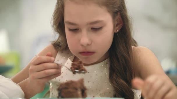 Hübsches Mädchen Schokolade Kuchen essen. Porträt von Kind Geburtstagskuchen Essen