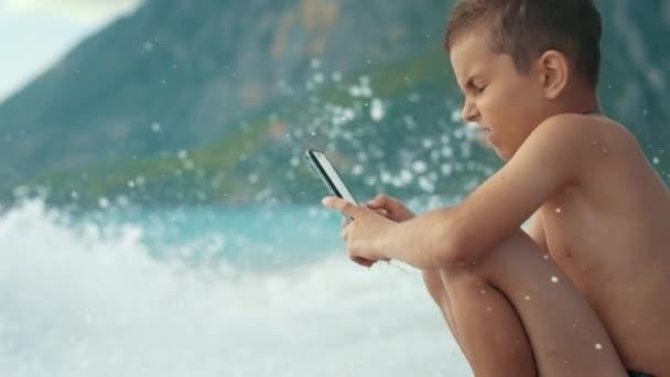 Boy pomocí mobilního telefonu sedí na moři pláž. Mořská vlna zasáhla chlapce s smartphone