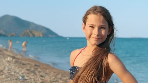 Smiling girl portrait on sea beach. Happy child posing on camera at vacations