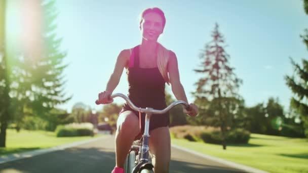 Sportovní žena jedoucí na kole na silnici park na slunečný den. Usmívající se žena školení na kole v létě parku. Happy cyklista Cyklistika venkovní