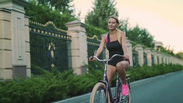 Young woman cycling on bicycle in summer park. Sport woman riding cycle