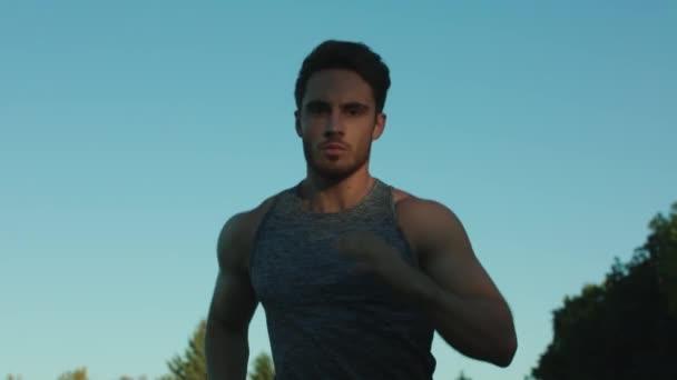 Mužské běžec tréninku kardio cvičení v parku. Sport muž běží na modré obloze