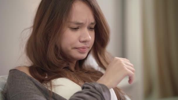 Kranke Frau niesen zu Hause. Nahaufnahme der jungen Frau niesen und husten im Schlafzimmer