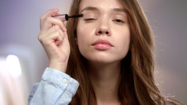Žena, která používá řasenku na řasy. Dívka, která používá krásu